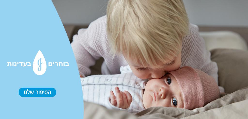 הילד מנשק את הלחי של התינוק