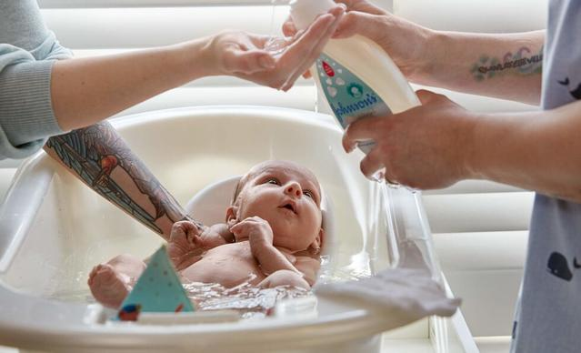 Bathing newborn with Johnson's® CottonTouch™ newborn wash & shampoo