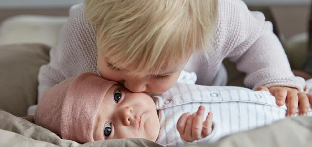 sibling kissing sister
